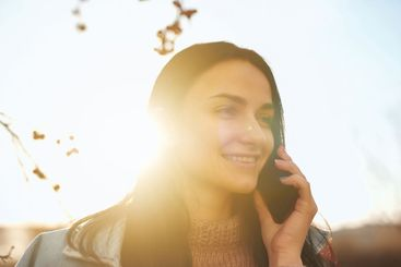 Lovely lady talking by phone in the lights of sunset