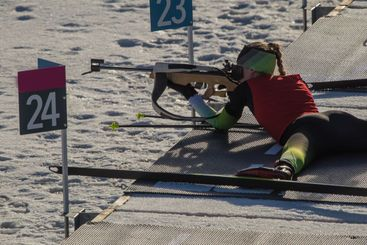 Female biathlon racer is lying on the ground and aiming...