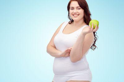 happy plus size woman in underwear with apple