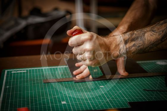 man working as artisan in his leather workshop, cutting...