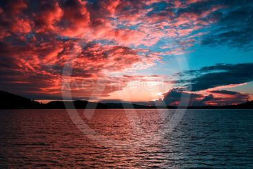 Crimson Sunrise Seascape with Water Reflections.