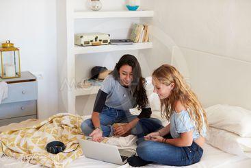 Two teenage girls sitting on bed using laptop computer