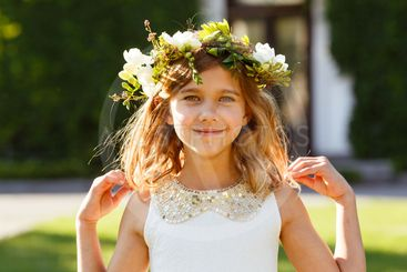 Beautiful girl with a wreath of fresh flowers