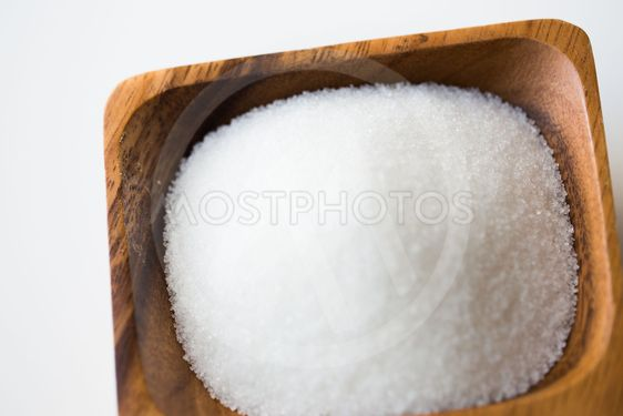 close up of white sugar heap in wooden bowl