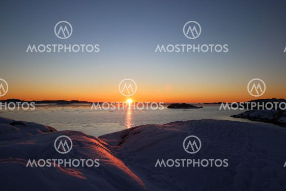 Solnedgång mot snötäckta klippor
