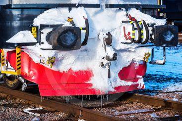 Vinter på järnvägen: Del av fronten på ett lok täckt med...