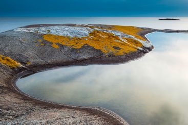 Smooth tide pool edged by mossy rock