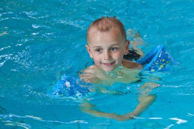 Pojke simmar med armpuffar