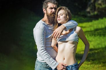 Young sexy couple standing in lawn with green grass...