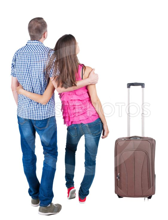 Back view of young couple traveling with suitcas .