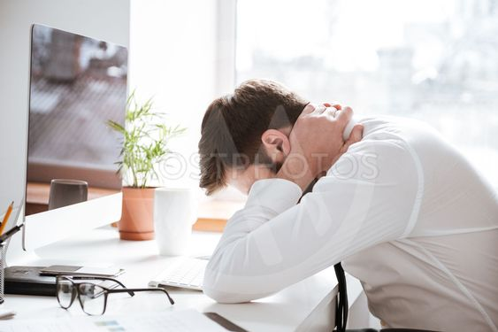 Tired young businessman with painful feelings holding neck.
