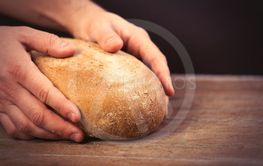 male hands holding bread loaf on the wonderful brown...