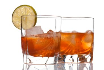glass of whiskey with ice cubes on white