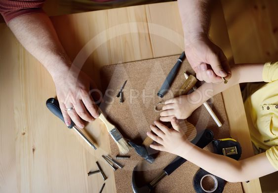 Mature man and little boy make a wooden toy together....