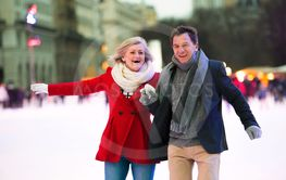 Beautiful senior couple ice skating in city centre. Winter