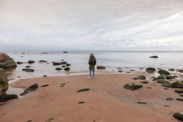 man in warm clothes  stands on a seashore