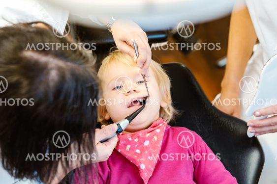 Woman dentist looking after baby teeth of a little girl