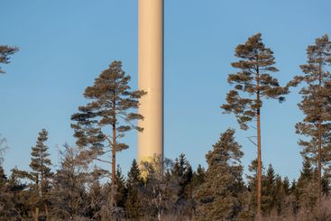 Column of wind mill among trees