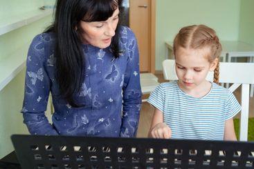 teacher teaches little girl to play on keyboard.