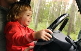 Happy little kid driving car with father