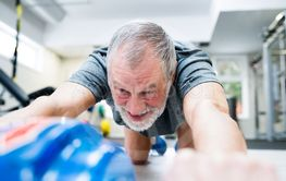Senior man in gym exercising abs with wheel roller