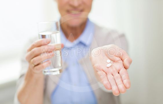 close up of senior woman with water and pills