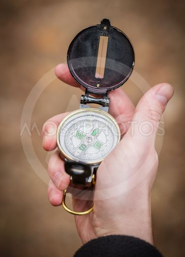 man wathing compass holding in his hands