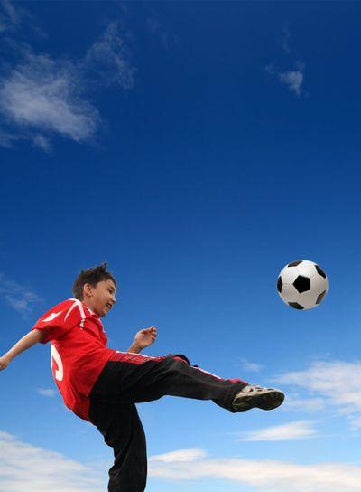 asian boy playing football
