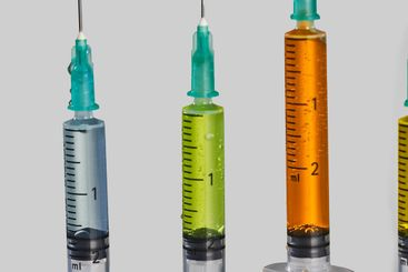 close-up of four syringes with colored vaccine