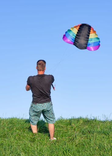 Man enjoying with big colorful kite at dike near Urk