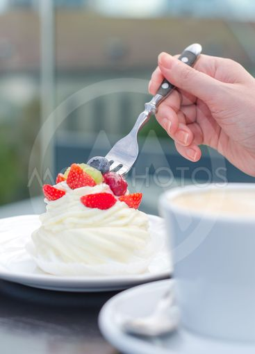 Coffee cup and creamy cake with berries