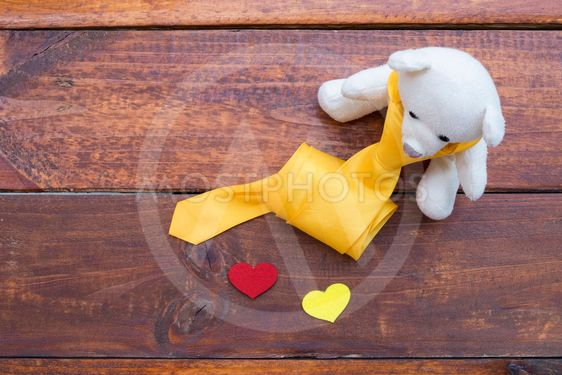 white teddy bear and heart on rustic wooden background