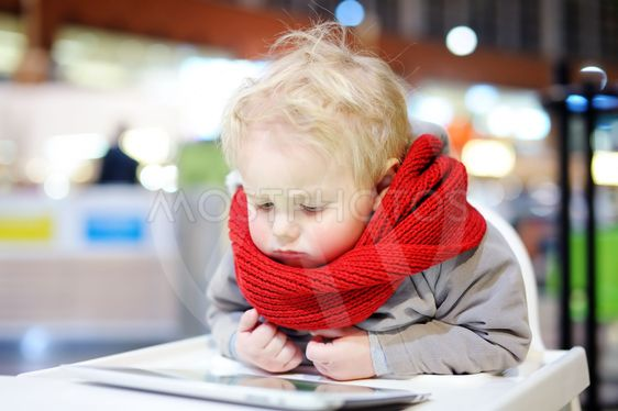 Toddler boy playing with a digital tablet