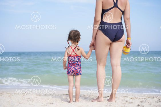 Mother daughter beach together rear view Unrecognizable...