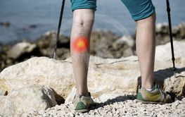 Woman with painful varicose veins on a leg with red dot...