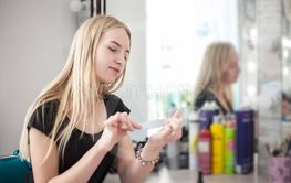 A woman is caring for her nails while sitting near a...