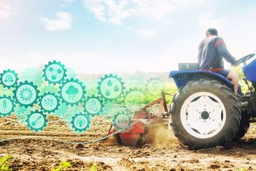 Farmer on a tractor cultivates a farm field and...