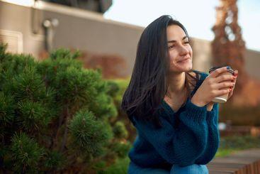 Dreamy female enjoying hot drink in a cosy city park