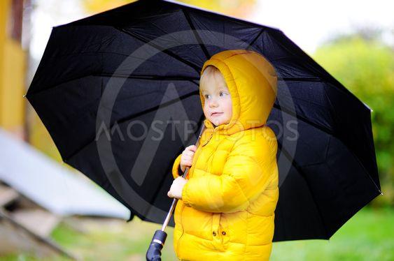 Child with big black umbrella in the rain