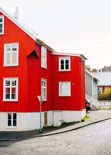 Red house with white roof on the street in Reykjavik,...