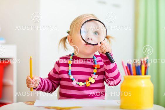 Toddler girl looking through magnifier