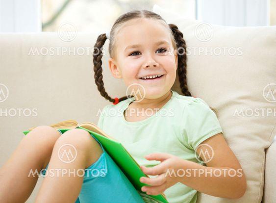 Little girl reads a book
