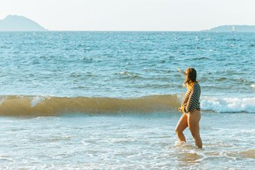 Young woman walking on the sea in the beach during a...