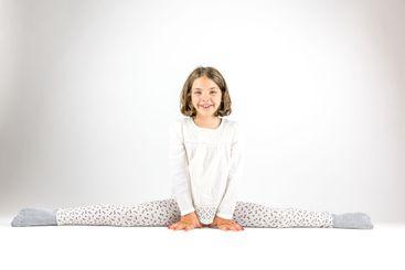 Ung flicka sitter i spagat mot vit bakgrund.