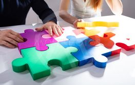 Two Businesspeople Solving Jigsaw Puzzle