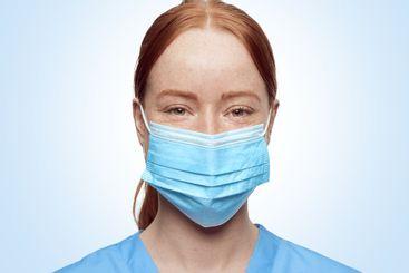 closeup portrait blue eyes Young nurse with masks...