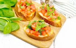 Bruschetta with tomato and spinach on white wooden table