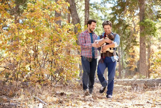 Gay Male Couple With Baby Walking Through Fall Woodland