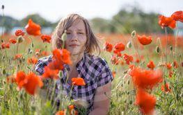 Portrait of smiling woman on poppy field