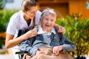 Senior woman in nursing home with nurse in garden